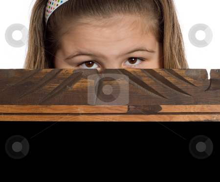 Peeking Child stock photo, Closeup view of a young girl peeking over the edge of a wooden frame by Richard Nelson