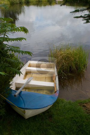 Rowboat stock photo, A blue and white rowboat on the shore of a pond, surrounded by nature. by Rick Parsons