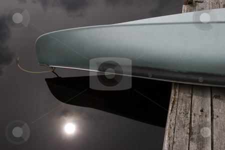 Canoe Close-Up stock photo, Close-up of a canoe, overhanging a wood dock, with the sun reflecting in the dark water. by Rick Parsons