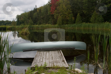 Canoe on a Dock stock photo, A blue canoe sits on a wood dock. by Rick Parsons