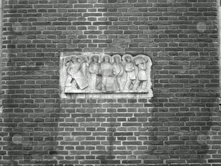 Brick wall with sculpture of people working stock photo, Brick wall  in Amsterdam with sculpture of people working by Jaime Pharr