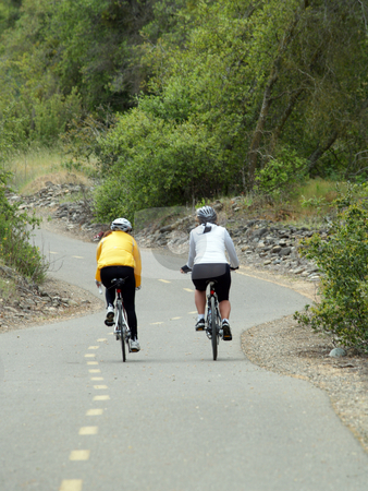 Two women on bikes on overcast day trail stock photo, Two women riding bikes on trail overcast day by Jeff Cleveland