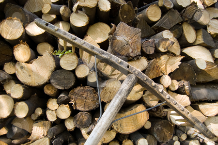 woodpile and rake stock photo, A woodpile of chestnut and beech for stoves and a rake by Roberto Marinello