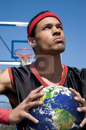 The World In Your Hands stock photo, A young basketball player gripping the earth tightly. by Todd Arena
