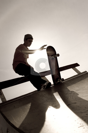 Skateboarder Silhouette stock photo, Silhouette of a young skateboarder at the top of the ramp. by Todd Arena