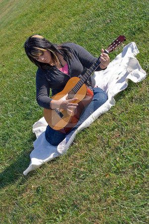 Woman Playing Her Guitar stock photo, A young Spanish woman playing a guitar outdoors. by Todd Arena