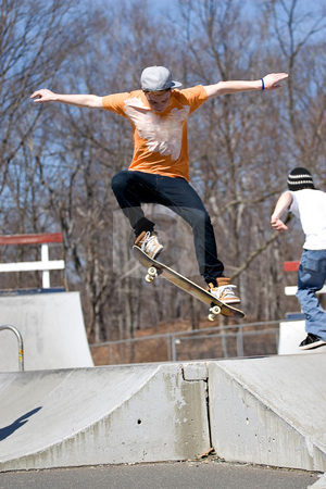 Skateboarder Jumping stock photo, Portrait of a young skateboarder performing a jump at the skate park. by Todd Arena