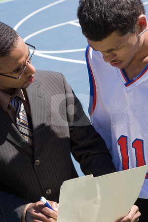 Basketball Coach stock photo, A basketball coach in a business suit sharing a play with a player on the team.   He could be also be recruiter trying to get him to sign a contract. by Todd Arena