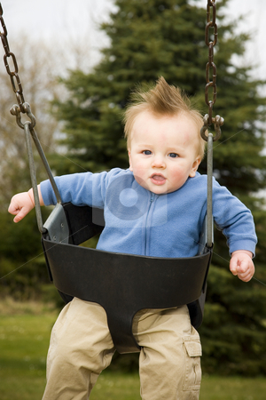 Happy Boy on Swing stock photo, A portrait of a happy boy on a swing in a playground. by Travis Manley