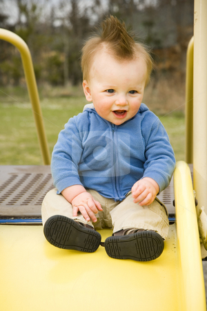 Happy Boy on Slide stock photo, A portrait of a happy boy on a slide in a playground. by Travis Manley