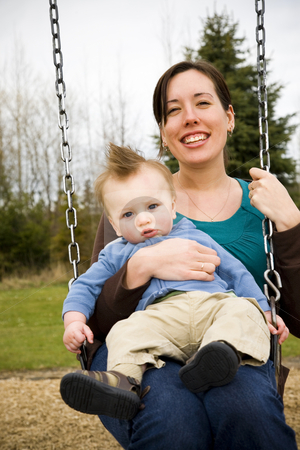 Mother and Son stock photo, A young mother and her son on a swing in a park having fun. by Travis Manley