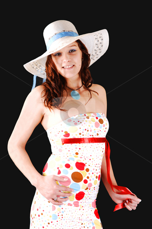 Pretty girl with hat. stock photo, Lovely woman in an colorful dress and a white hat over black background. by Horst Petzold