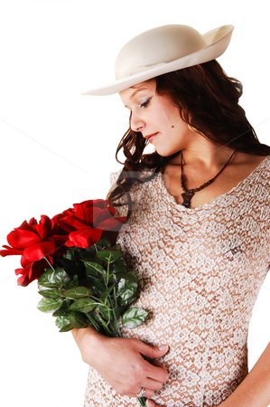 Woman with hat and red roses. stock photo, Beautiful lady in a beige long dress and hat standing in the studio with  red roses in her arm smiling, for white background. by Horst Petzold