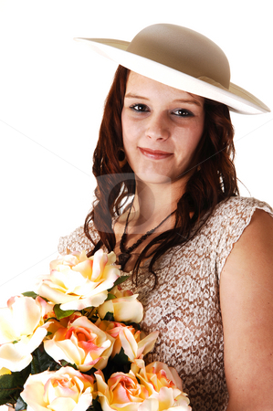 Woman with hat and roses. stock photo, Beautiful lady in a beige long dress and hat standing in the studio with  yellow roses in her arm smiling, for white background. by Horst Petzold