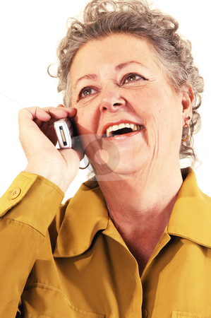 Senior woman on the cell phone. stock photo, A senior woman in an dark yellow jacket talking on the cell phone and smiling. On white background. by Horst Petzold