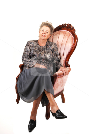 Senior woman in pink armchair. stock photo, All dressed up elderly woman sitting in an pink armchair, enjoying her life,  for white background.. by Horst Petzold
