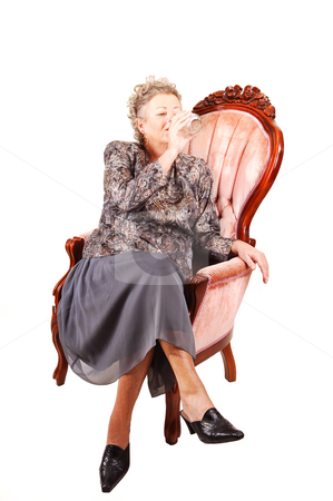 Senior woman in pink armchair. stock photo, All dressed up elderly woman sitting in an pink armchair, enjoying her life and having a glass of water, for white background.. by Horst Petzold