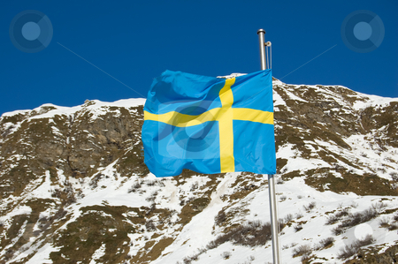 Swedish Flag stock photo, A Swedish Flag is waving in the mountain wind by Roberto Marinello