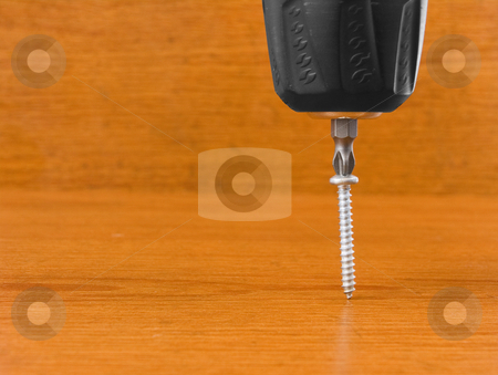 Screw driver and screw stock photo, Screw driver and screw on a wooden background by John Teeter