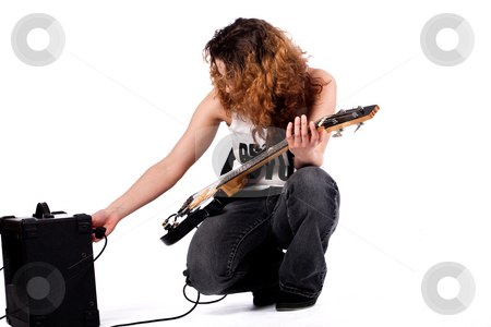 Posing and playing with my guitar stock photo, Young girl adjusting her guitar and amplifier by Frenk and Danielle Kaufmann