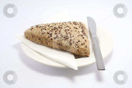 Sesame Seed Bread Roll stock photo, Seeded bread roll on a plate with paper napkin and knife by Helen Shorey