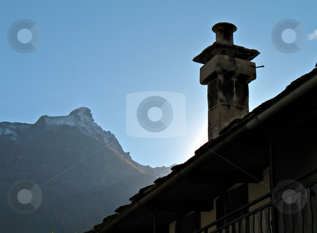 Chimney sunset stock photo, A chimney of an old country house, mountains in background by Roberto Marinello