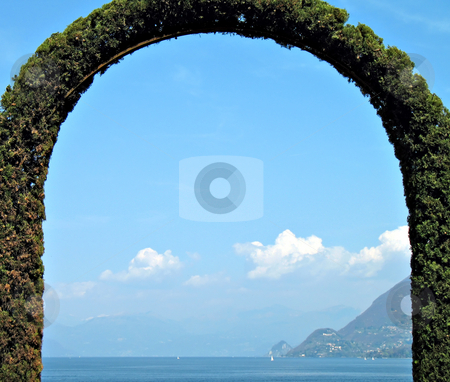 Hedge arch shaped stock photo, A fence arch-shaped in front of the lake. lago Maggiore, Italy by Roberto Marinello