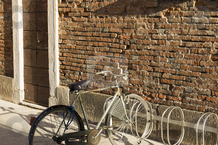 Bike at the wall stock photo, A bike parked near a red brick wall by Roberto Marinello