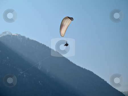 White Paraglide stock photo, A paraglider il flying in the blue sky near a mountain with his paraglide by Roberto Marinello