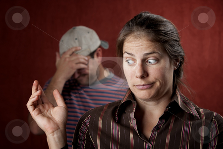 Upset man and guilty woman stock photo, Guilty woman with upset man in the background by Scott Griessel