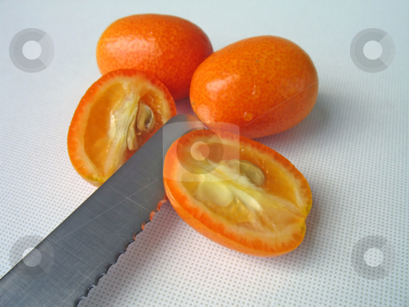 Cutting tangerines stock photo, Cutting tangerines (kumquat), knife by Roberto Marinello