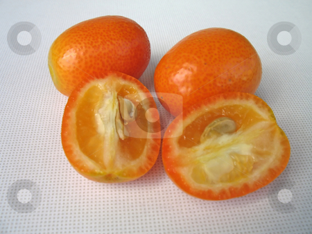 Cutting tangerines stock photo, Cutting tangerines (kumquat) by Roberto Marinello