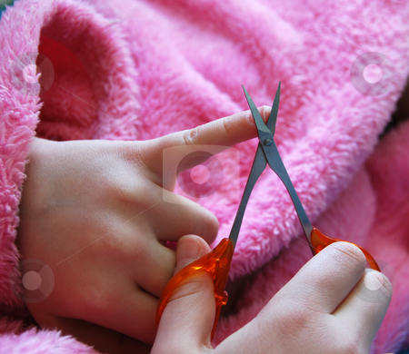 Child cuts nails stock photo, Girl in pink garment cutting her nails with cosmetic scissors by Leyla Akhundova