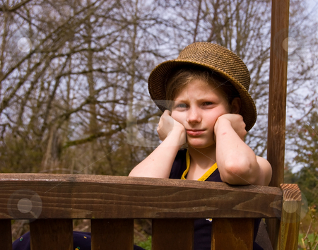 Girl Pouting stock photo, This 8 year old Caucasian girl is pouting while sitting on an outdoor swing wearing a natural hat. by Valerie Garner