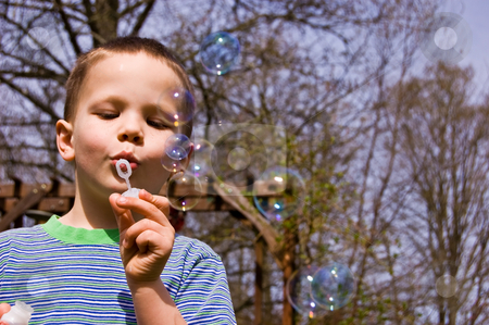 Young 4 Year Old Boy Blowing Bubbles stock photo, This young 4 year old boy is having a great time blowing bubbles outdoors. by Valerie Garner