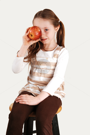 Little girl with apple. stock photo, An little girl sitting on a high chair and holding a red apple on her right eye. by Horst Petzold