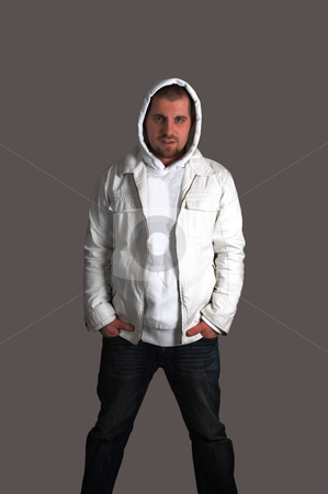 Young man on dark background. stock photo, An young man with his hands in the pocket and a white jacket with a hood on his head for dark gray background. by Horst Petzold