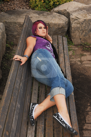 Girl lying on park bench. stock photo, An red hair girl in jeans lying on the park bench with big rocks around. by Horst Petzold