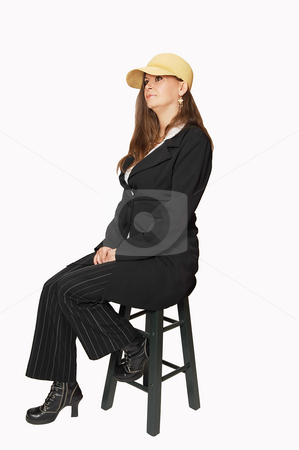 Sitting woman in black pants and coat and beige hat.. stock photo, A young pretty woman sitting in a business suit and beige hat, for white background and shooing her great figure. by Horst Petzold