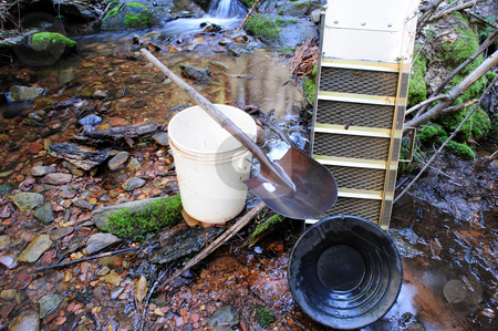 Gold Prospecting Tools stock photo, Basic tools used for placer gold prospecting. These include a gold pan, sluice box, 5 gallon plasic bucket and a shovel. A peaceful mountain stream is used for a backdrop for these ancient but modern in the materials used to make them. by Lynn Bendickson