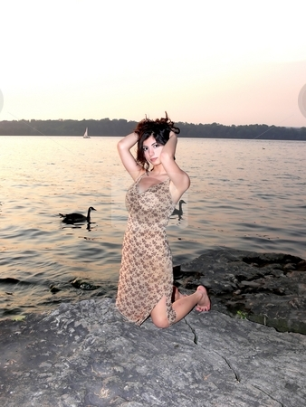 Lady on the lake in sunset  stock photo, An lovely young lady kneeling on a big rock on the lake and try to fix her hair on a nice sunset. by Horst Petzold