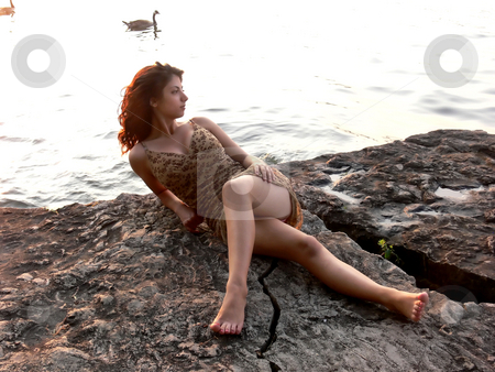 Lady on the lake   stock photo, An lovely young lady sitting on a big rock on the lake relaxing by sunset. by Horst Petzold