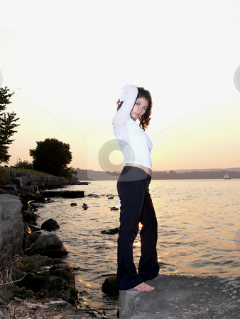 Lady on the lake  stock photo, A beautiful young girl standing on a rock on the lake and enjoying the sunset. by Horst Petzold