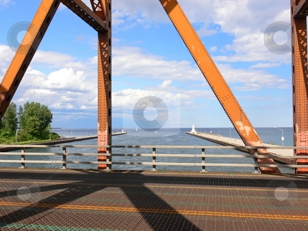 Old lift bridge  stock photo, The view trough an loft bridge over the canal to the harbor of Hamilton on a nice sunny day. by Horst Petzold