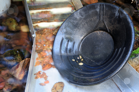 Gold Pan And Nuggets stock photo, Black plastic gold pan with 6 gold nuggets inside a sluice box with some water flowing through it. by Lynn Bendickson