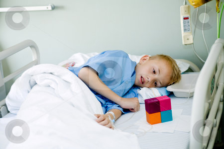 Sick boy in hospital bed looking at his toy stock photo, Portrait of a sick young boy after an operation in his hospital bed. by Frenk and Danielle Kaufmann