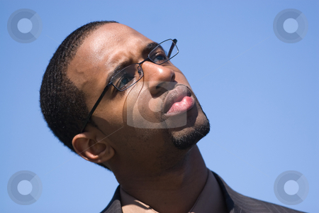 Business Man Thinking stock photo, African American man wearing glasses and a business suit isolated over a blue background. by Todd Arena