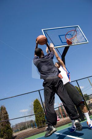 Man Playing Basketball stock photo, A young basketball player going for a jump shot. by Todd Arena