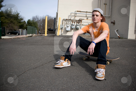 Skateboarder Resting stock photo, A young skater resting on his board. by Todd Arena