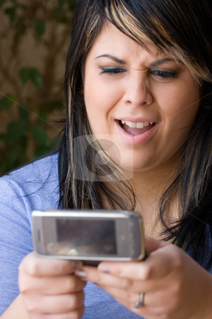 Text Messaging Gossip stock photo, A young woman shocked at what she is reading on her cell phone.  Shallow depth of field. by Todd Arena
